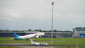 Traffic at Shiphol Airport. AMSTERDAM, THE NETHERLANDS - JULY 29, 2017: Garuda Indonesia Boeing 777 PK-GIA take-off and FlyBe Bombardier Dash 8 G-ECOF taxiing stock video