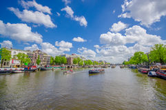 Amsterdam, Netherlands - July 10, 2015: Large water channel running through city with several boats parked alongside Stock Image