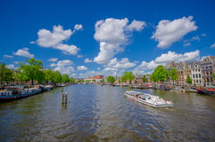 Amsterdam, Netherlands - July 10, 2015: Large water channel running through city with several boats parked alongside Royalty Free Stock Image