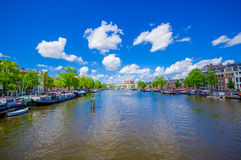 Amsterdam, Netherlands - July 10, 2015: Large water channel running through city with several boats parked alongside Royalty Free Stock Photography