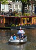 People travel by boat along the canals of Amsterdam at summer time. Royalty Free Stock Image