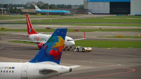 Airplane taxiing after landing. AMSTERDAM, THE NETHERLANDS - JULY 29, 2017: SmallPlanet Airlines Airbus A320 LY-SPA taxiing after landing, and Corendon Boeing stock footage