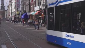 Street of Amsterdam scene. AMSTERDAM, THE NETHERLANDS - JULY 28, 2017: Street scene with modern tram in Amsterdam, tram is quickest way to get into and around stock video
