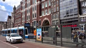 Street of Amsterdam scene. AMSTERDAM, THE NETHERLANDS - JULY 28, 2017: Street scene with modern tram in Amsterdam, tram is quickest way to get into and around stock footage