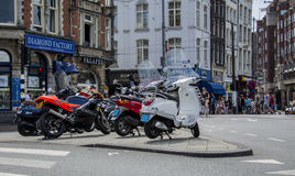 Amsterdam, Netherlands - July 19th, 2014: Scooters parked in Amsterdam. Amsterdam, Netherlands - July 19th, 2014: A row of mopeds / scooters parked on a street Royalty Free Stock Photos