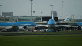 Tow tractor pushes Boeing 747 of KLM. Amsterdam, Netherlands - July 26, 2017: Tow tractor pushes Boeing 747 jumbojet of KLM airlines in Schiphol airport stock footage