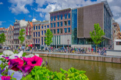 Amsterdam, Netherlands - July 10, 2015: Traditional Dutch city blocks with charming red brick buildings next to water Royalty Free Stock Photos