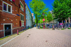 Amsterdam, Netherlands - July 10, 2015: Typical charming street of bridgestone surface, traditional Dutch buildings Royalty Free Stock Image