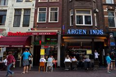 AMSTERDAM, THE NETHERLANDS - JUNE 10, 2014: Beautiful sreets of Amsterdam with outdoors cafe on summer day Royalty Free Stock Images