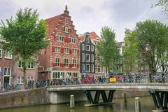 AMSTERDAM, NETHERLANDS - JUNE 25, 2017: Old buildings near the one of the water canals in the historical part. Old buildings near the one of the water canals in royalty free stock images