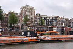 AMSTERDAM, NETHERLANDS - JUNE 25, 2017: Orange boats of the Canal Lovers Cruises. Boating along the canals of Amsterdam is one of the popular types of tourist Royalty Free Stock Photography