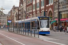 AMSTERDAM, NETHERLANDS - JUNE 25, 2017: Siemens Combino tram on. The Damrak street in center of city. The Amsterdam Tram is the largest tram network in the Stock Image