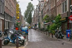 AMSTERDAM, NETHERLANDS - JUNE 25, 2017: View of the one of the town street under the rain in the historical part. View of the one of the town street under the royalty free stock photos