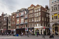 AMSTERDAM, NETHERLANDS - JUNE 25, 2017: View to the old historical buildings on the Damrak street in Amsterdam. On the street there are cultural centers, many Stock Photography