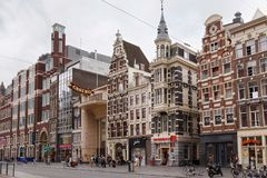 AMSTERDAM, NETHERLANDS - JUNE 25, 2017: View to the old historical buildings on the Damrak street in Amsterdam. On the street there are cultural centers, many Stock Photos
