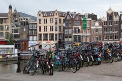 AMSTERDAM, NETHERLANDS - JUNE 25, 2017: View to the old historical buildings on the Damrak street in Amsterdam. On the street there are cultural centers, many Royalty Free Stock Photo