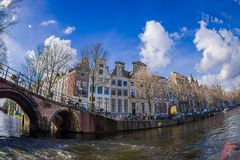 AMSTERDAM, NETHERLANDS, MARCH, 10 2018: Beautiful outdoor view Amsterdam canals with bridge and typical dutch houses Royalty Free Stock Image