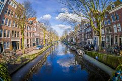 AMSTERDAM, NETHERLANDS, MARCH, 10 2018: Beautiful outdoor view of houses and Boats on Amsterdam Canal Royalty Free Stock Images