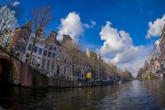 AMSTERDAM, NETHERLANDS, MARCH, 10 2018: Beautiful outdoor view Amsterdam canals with bridge and typical dutch houses Stock Photos