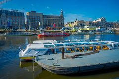 AMSTERDAM, NETHERLANDS, MARCH, 10 2018: Boats in the canals of Amsterdam. Amsterdam is the capital and most populous. City of the Netherlands with a building Royalty Free Stock Images