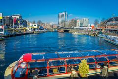 AMSTERDAM, NETHERLANDS, MARCH, 10 2018: Boats in the canals of Amsterdam. Amsterdam is the capital and most populous. City of the Netherlands with a building Stock Photos