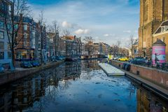 AMSTERDAM, NETHERLANDS, MARCH, 10 2018: Gorgeous view of some cars parked in the street close to many boats in the. Canals of Amsterdam, is the capital and most Stock Photography