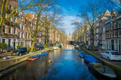 AMSTERDAM, NETHERLANDS, MARCH, 10 2018: Gorgeous view of some cars parked in the street close to many boats in the. Canals of Amsterdam, is the capital and most Royalty Free Stock Photography