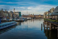 AMSTERDAM, NETHERLANDS, MARCH, 10 2018: Gorgeous view of some cars parked in the street close to many boats in the. Canals of Amsterdam, is the capital and most Royalty Free Stock Photos