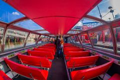 AMSTERDAM, NETHERLANDS, MARCH, 10 2018: Indoor view of red excursion boat or cruise ship on Amsterdam water canal in the. Center of Amsterdam, Amstel river Royalty Free Stock Photography