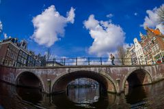 AMSTERDAM, NETHERLANDS, MARCH, 10 2018: Outdoor view of Amsterdam canals with people walking over a bridge and typical Stock Photos