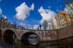 AMSTERDAM, NETHERLANDS, MARCH, 10 2018: Outdoor view of Amsterdam canals with people walking over a bridge and typical Stock Photography
