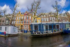 AMSTERDAM, NETHERLANDS, MARCH, 10 2018: Outdoor view of houseboats and apartment buildings behind on a canal in the city Stock Photo