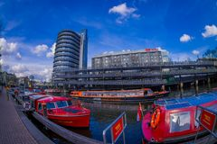 AMSTERDAM, NETHERLANDS, MARCH, 10 2018: Outdoor view of red excursion boat or cruise ship on Amsterdam water canal in. The center of Amsterdam, Amstel river Stock Image