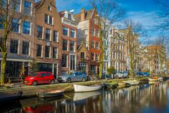 AMSTERDAM, NETHERLANDS, MARCH, 10 2018: Outdoor view of some cars parked in the street close to a boats in the canals of. Amsterdam, is the capital and most Stock Photo