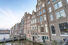 AMSTERDAM, THE NETHERLANDS - MARCH 2015: View of city buildings. Along canal. The city hosts 15 million tourists annually royalty free stock photography