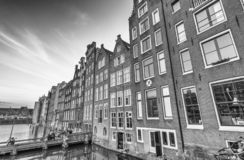 AMSTERDAM, THE NETHERLANDS - MARCH 2015: View of city buildings. Along canal. The city hosts 15 million tourists annually royalty free stock image