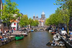Amsterdam, Netherlands - May, 2018: Church of St Nicholas with old town canal during spring sunny day in Amsterdam, Netherlands stock photos