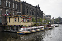 Amsterdam. NETHERLANDS - MAY, 13, 2017: Jetty and box office for boats that run through tourist-loaded canals Royalty Free Stock Photos