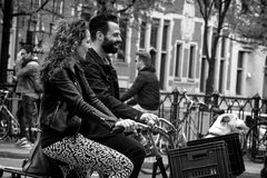 AMSTERDAM, NETHERLANDS - MAY 9: Man and woman with dog riding bicycles Royalty Free Stock Photo