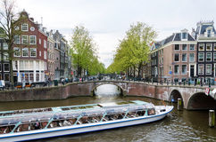 Amsterdam, Netherlands - May 7, 2015: Passenger boats on canal tour in the city of Amsterdam. Royalty Free Stock Images
