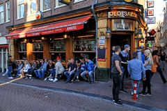 Tourists and local people enjoy the datch pub in red light district, Amsterdam, Netherlands. AMSTERDAM, NETHERLANDS - MAY 5, 2016: Tourists and local people royalty free stock photography