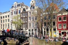 People relax along a canal in famous red light neighborhood, Amsterdam, Netherlands. stock photos