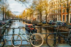 Bicycles and Dutch Houses On Amsterdam Canal In Autumn. AMSTERDAM, NETHERLANDS - NOVEMBER 13, 2017: Bicycles and Dutch Houses On Amsterdam Canal In Autumn Stock Photo