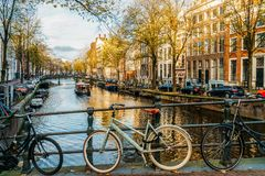 Bicycles and Dutch Houses On Amsterdam Canal In Autumn. AMSTERDAM, NETHERLANDS - NOVEMBER 13, 2017: Bicycles and Dutch Houses On Amsterdam Canal In Autumn Royalty Free Stock Images