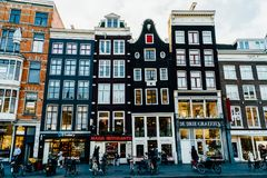 People Walking In Downtown Amsterdam Admiring Beautiful Architecture Of Dutch Houses In Autumn. AMSTERDAM, NETHERLANDS - NOVEMBER 13, 2017: People Walking In Stock Images