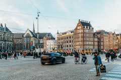 People Walking In Downtown Amsterdam Admiring Beautiful Architecture Of Dutch Houses Royalty Free Stock Photography