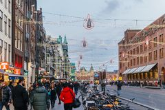 People Walking In Downtown Amsterdam Admiring Beautiful Architecture Of Dutch Houses Stock Photo