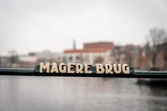Selective focus of a bridge steel rail with a sign of the famous Magere Brug in Amsterdam. AMSTERDAM, NETHERLANDS - NOVEMBER 22, 2018: Selective focus of a royalty free stock image
