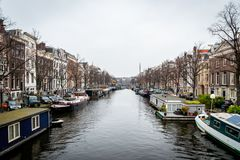 Perspective city view of buildings and many houseboats on a canal in Amsterdam. royalty free stock image