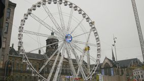 AMSTERDAM, NETHERLANDS - 16 oct 2016, amusement Park - Ferris wheel on Dam Square - historical center of Holland CAPITAL. Telephoto shot stock video